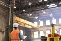 Steel worker with clipboard looking up in factory — Stock Photo
