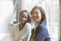 Портрет уверенно улыбающихся деловых женщин в современном офисе — стоковое фото