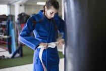 Giovane donna stringendo cintura di judo a sacco da boxe in palestra — Foto stock