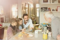 Male gay parents and children using laptop at breakfast kitchen counter — Stock Photo
