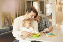 Male gay parents feeding baby son and using digital tablet — Stock Photo