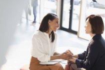 Улыбающиеся деловые женщины держатся за руки в солнечном вестибюле офиса — стоковое фото
