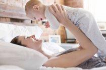 Lächelnde Mutter hält Baby-Tochter über Kopf auf Bett — Stockfoto