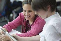 Lächelnde Schüler mit digitalem Tablet im Klassenzimmer — Stockfoto