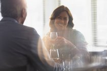 Smiling mature couple drinking wine, dining at restaurant table — Stockfoto