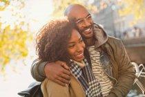 Pareja sonriente, cariñoso abrazando y mirando lejos - foto de stock