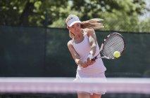Determinado joven mujer tenis jugador jugando tenis, golpeando la bola en cancha de tenis sol - foto de stock