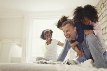 Multi-ethnic daughters tackling father on bed — Stock Photo