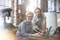 Portrait confident designers working at laptop in workshop — Stock Photo