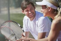 Sonriendo de tenistas masculinos y femeninos descansando y hablando con raquetas de tenis en exteriores soleados - foto de stock