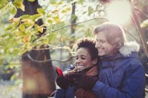 Smiling couple using cell phone in sunny autumn park — Stock Photo
