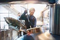 Male coffee roaster checking tank — Stock Photo