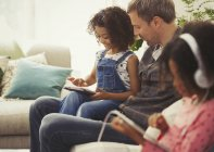 Multi-ethnic father and daughter using digital tablet on sofa — Stock Photo