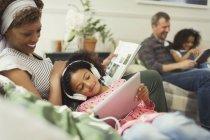 Mother cuddling daughter with headphones using digital tablet — Stockfoto