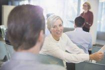 Femme d'affaires souriant parlant à l'homme d'affaires dans l'auditoire de la Conférence — Photo de stock
