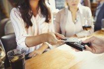 Frau bezahlt Barkeeper mit Kreditkarte kontaktloses Bezahlen an Bar — Stockfoto