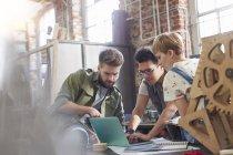 Jeunes designers travaillant à l'ordinateur portable en atelier — Photo de stock