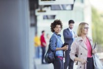 Woman holding digital tablet and waiting for train in station — Stockfoto