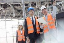 Бизнесмен и инженер беседуют на строительной площадке — стоковое фото