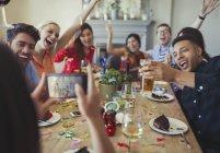 Frau mit Kamera-Handy fotografieren spielerisch Freunde werfen Konfetti am Tisch im restaurant — Stockfoto