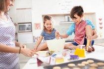 Mère et enfants cuisiner des biscuits dans la cuisine — Photo de stock