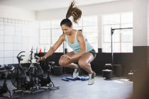 Young woman doing jump squats in gym — Stock Photo