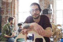 Портрет уверенный мужчина дизайнер с татуировками опираясь на прототип в мастерской — стоковое фото