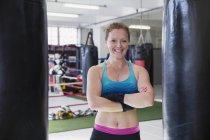 Boxer femmina ritratto sorridente, fiducioso in piedi a sacchi da boxe in palestra — Foto stock