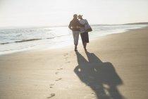 Liebevolles reifes Paar, das sich umarmt und am sonnigen Strand spaziert — Stockfoto