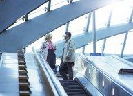 Business people riding escalator — Stock Photo
