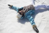 Happy woman making snow angels — Stock Photo