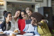 Smiling women friends taking selfie at restaurant table — Stock Photo
