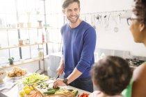 Glückliche Familie bereitet Mahlzeit in der heimischen Küche zu — Stockfoto