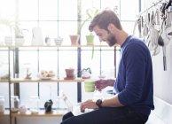 Молода людина, що сидить на кухонного столу з кухля і ноутбук — стокове фото