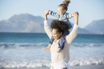 Mother carrying daughter on her shoulders on beach — Stock Photo
