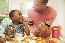Smiling father and son decorating Easter eggs and cookies — Stock Photo