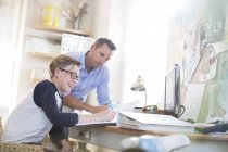 Father helping teenage son doing his homework in room — Stock Photo