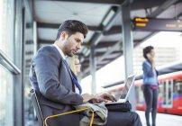 Businessman using laptop at train station — Stock Photo