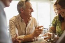 Smiling mature couple drinking wine, dining at restaurant table — Stock Photo