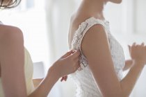Bridesmaid helping bride with dressing in domestic room — Stock Photo