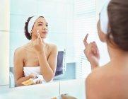 Aplicação de hidratante para o rosto no espelho do banheiro de mulher — Fotografia de Stock