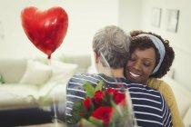 Esposa marido abrazos da globo del día de San Valentín y ramo de rosa - foto de stock