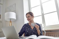 Smiling businesswoman drinking coffee and working at laptop — Stock Photo