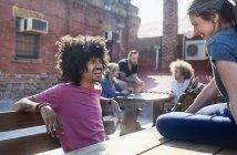 Улыбающиеся друзья болтают на солнечной городской крыше — стоковое фото