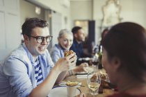 Friends talking and eating at restaurant table — Stock Photo