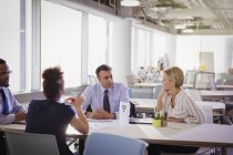 Business people talking at table in shared workspace — Stock Photo