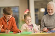 Father and children bonding, doing crafts at table — Stock Photo