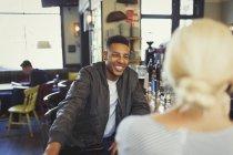 Smiling man talking to woman in bar — Stock Photo