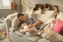 Exhausted father and baby son sleeping on sofa — Stock Photo