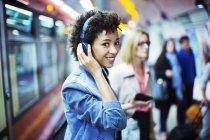 Femme souriante à l'écoute au casque dans le métro — Photo de stock